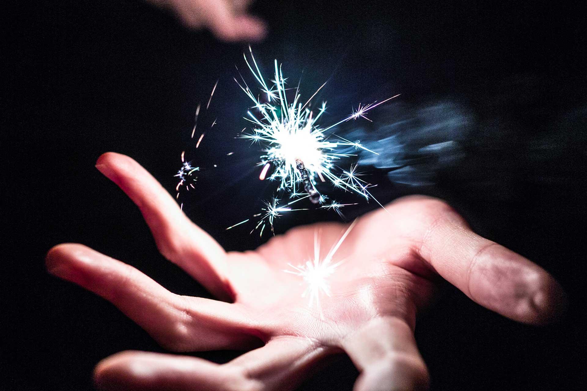 Image d'une main dans le noir éclairé par une étincelle