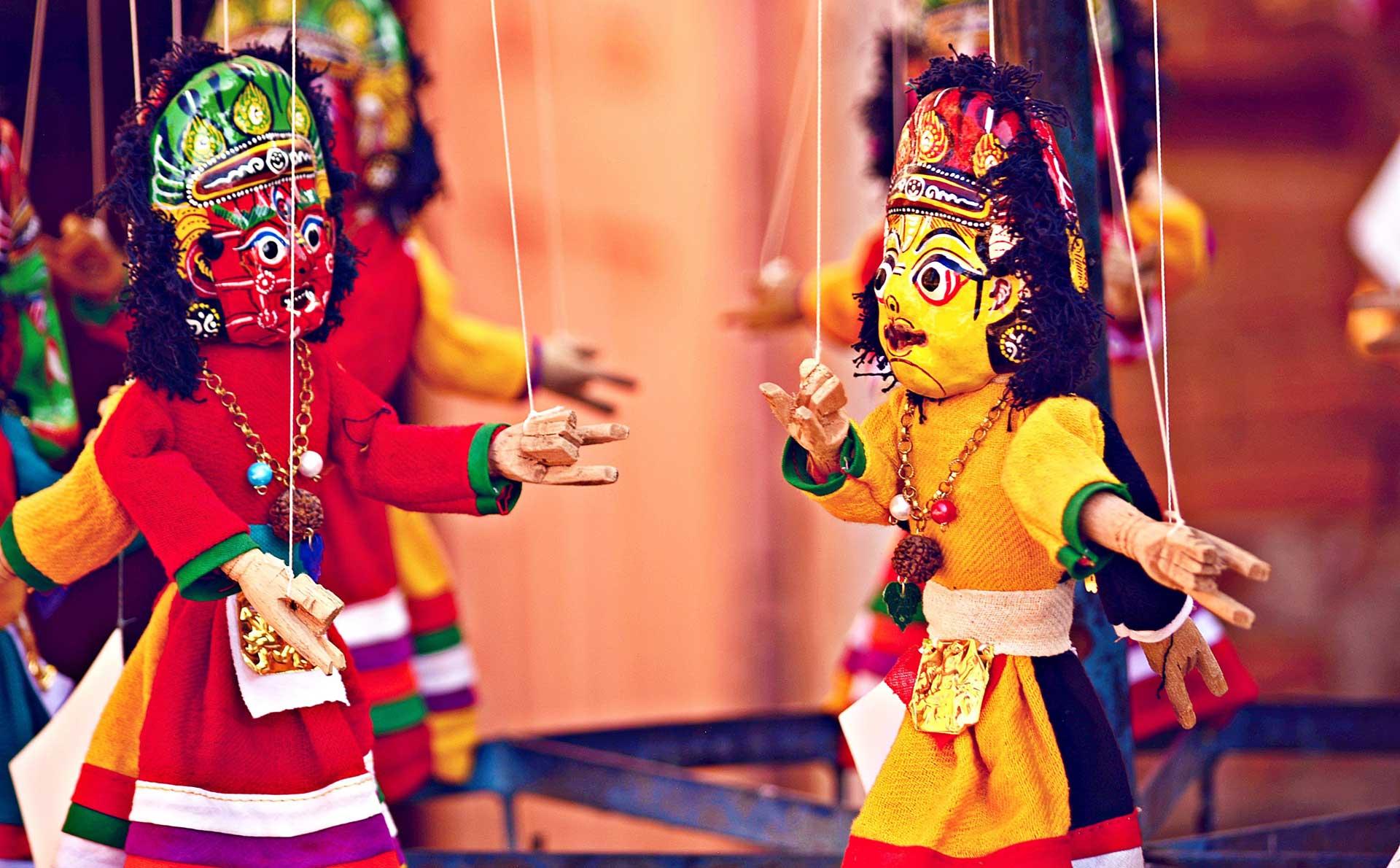 Image de deux marionnettes, une rouge a gauche et une jaune sur la droite