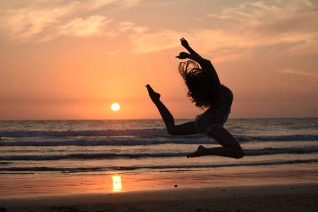 Image d'une femme qui danse au bord de la plage